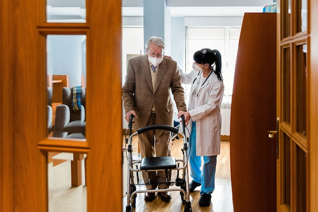Nurse in white coat holding the hand of an elderly man with a walker indoors