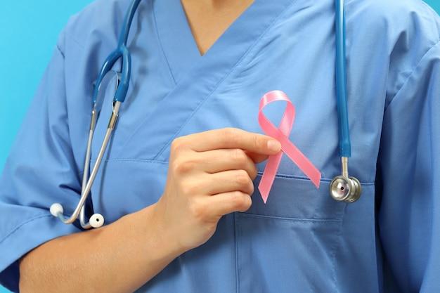 Медсестра с лентой осведомленности рака груди, крупным планом