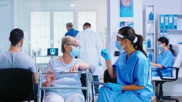 Медсестра с козырьком от коронавируса в зоне ожидания больницы объясняет диагноз пожилой женщине-инвалиду с ходунками. система здравоохранения во время глобальной пандемии.