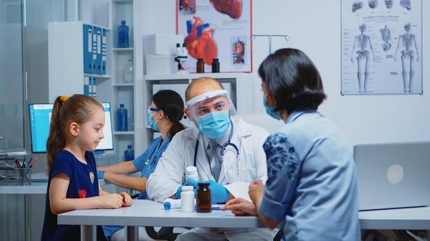 바이저와 장갑을 끼고 의사에게 알약을 주는 간호사. covid-19 동안 병원 캐비닛에서 의료 서비스 상담 검사를 제공하는 보호 마스크를 갖춘 소아과 전문의