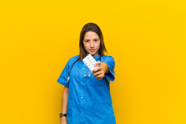 Nurse woman with pils against orange wall