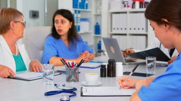 간호사가 클립보드에 글을 쓰는 동안 전문 팀 작업자는 사무실에서 브레인스토밍을 하며 의료 회의를 하고 있습니다. 회의실에서 환자의 증상을 검사하는 전문 의사.