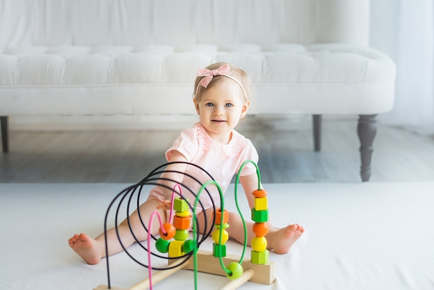 Nursery baby girl playing with educational logic toy