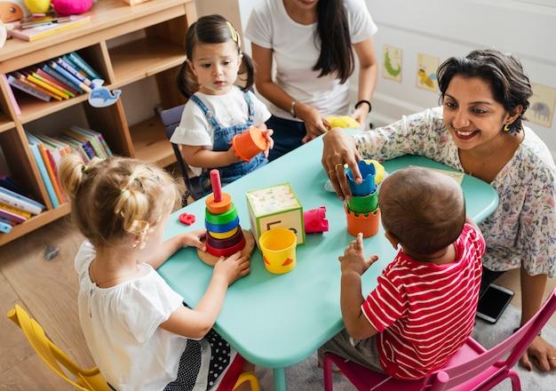 教室で先生と遊んでいる保育園の子供たち