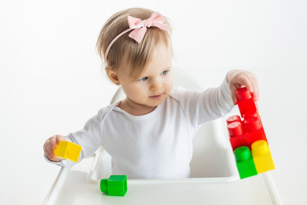 Nursery kid plays with educational toys in classroom sitting at the table in baby chair. cute little girl playing colorful construction blocks. white background.