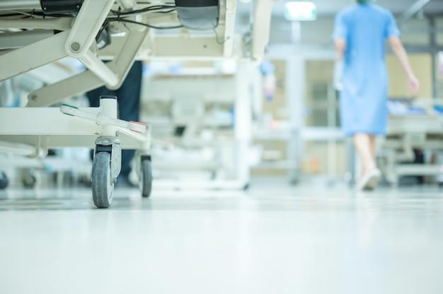 看護師は患者を診察し、icu室の清潔さをチェックするために歩いています。