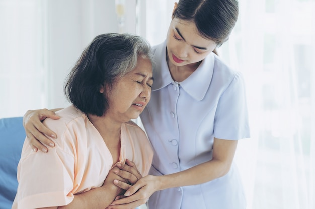 The nurses are well good taken care of elderly woman patients in hospital bed patients