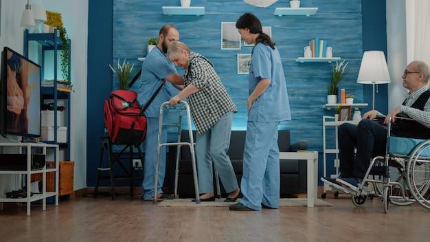 Nurses helping disabled pensioner to use walk frame