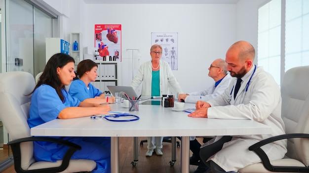 간호사는 환자 진단에 대해 설명하고 병원 회의실에서 메모하는 동안 의료 전문가의 말을 듣고 있습니다. 질병에 대해 동료와 이야기하는 클리닉 치료사, 전문 전문가