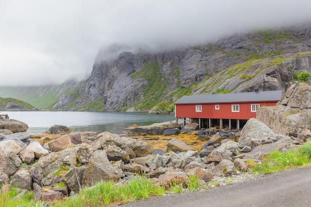 Настоящая рыбацкая деревня нус-фьорд с традиционными красными домами рорбу зимой. лофотенские острова, норвегия