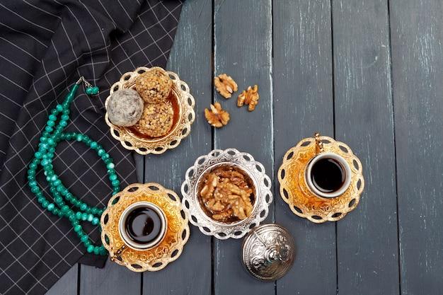 暗い木製のテーブル、トップビューでコーヒーを添えてナッツボールデザート