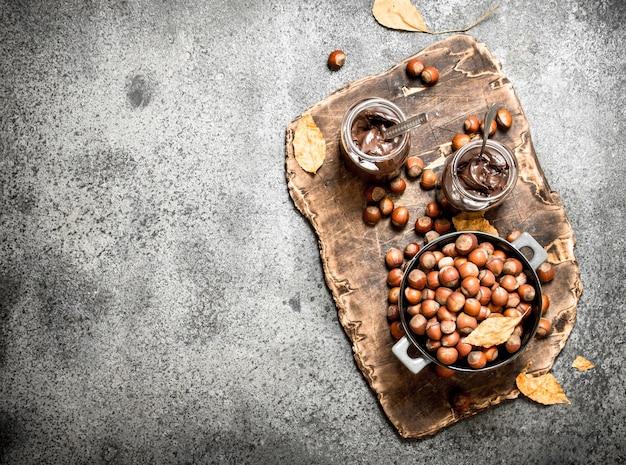 Ореховое масло из фундука и шоколада на деревенском фоне