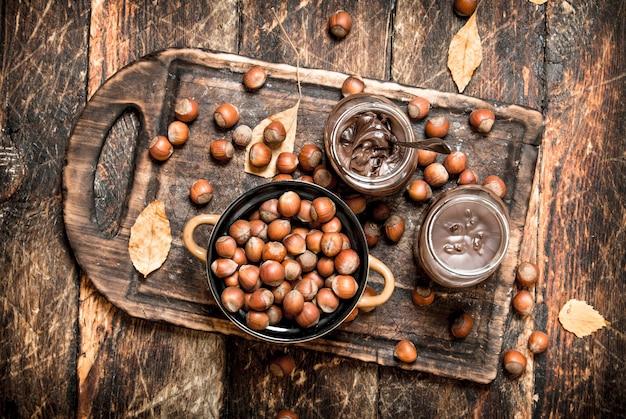 木製の背景にチョコレートとヘーゼルナッツとナッツバター