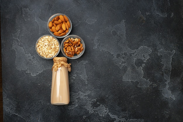Nut milk and heaps of different nuts top view on wooden desk