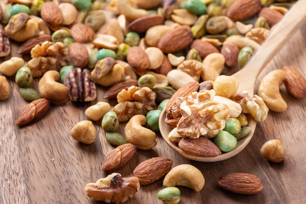 Nut mix on wooden spoon, assorted and various of nuts healthy diet.