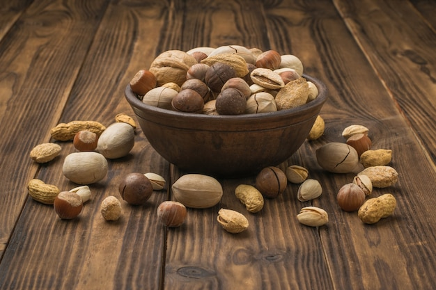 The nut mixture is poured out of an earthenware bowl on a dark wooden table. vegetarian food.
