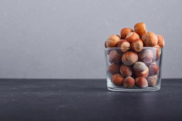 Gusci di noci in una tazza di vetro su sfondo grigio sul lato destro.