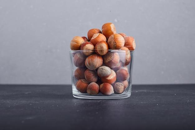 灰色の背景にガラスのカップのナッツの殻。