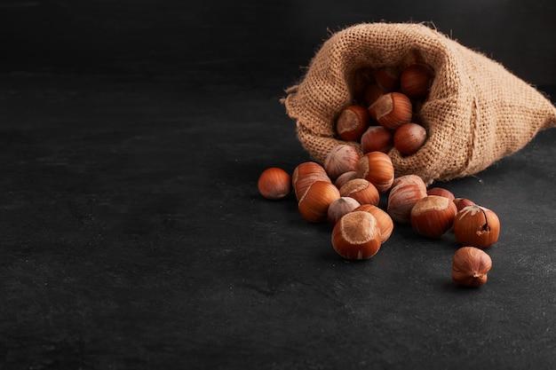 黒の背景に素朴な小包からナッツの殻。