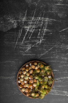Nut shells in a wooden platter on black background