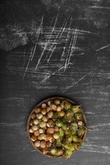 Gusci di noci in un piatto di legno su sfondo nero