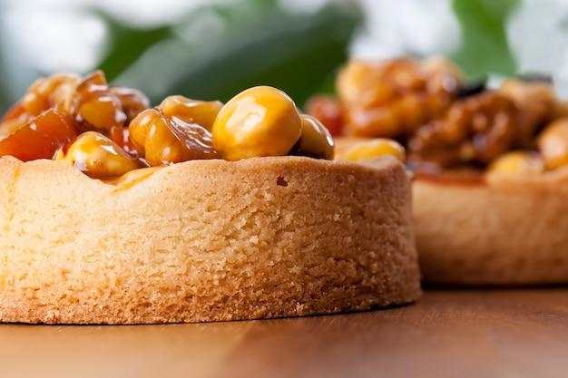液体キャラメルの層で覆われたナッツのタルト、天然成分を含む生地で作られた高カロリーのデザート、ヘーゼルナッツ、ピーナッツ、クルミ、ドライフルーツを詰めたタルト
