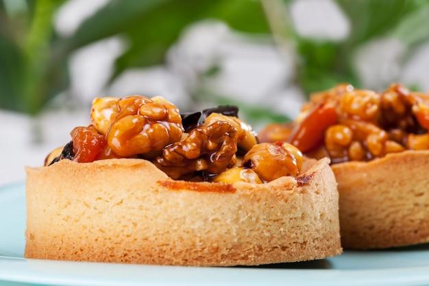 Ореховая тарталетка, покрытая слоем жидкой карамели, калорийный десерт из теста с натуральными ингредиентами, тарталетка с начинкой из фундука, арахиса и грецких орехов и сухофруктов