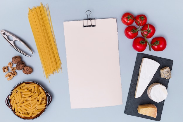 Nutcracker; walnut; raw pasta; various cheese; and tomato with blank white paper on grey surface