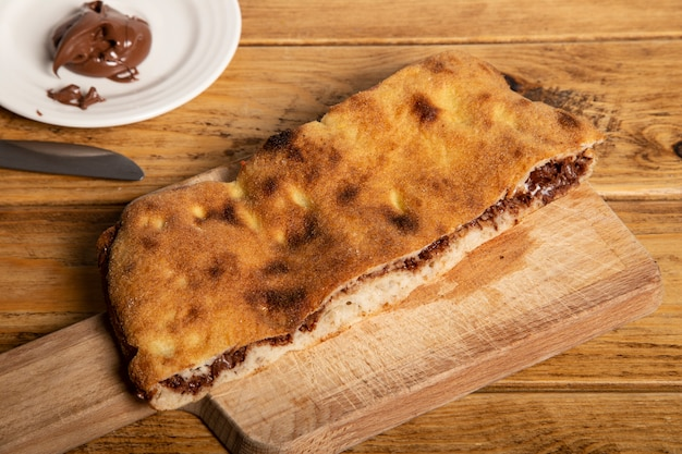 Сладкая nutella детская пицца на деревянной разделочной доске.