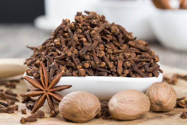 ナツメグ、アニス、クローブのスパイスがキッチンの古い木製のテーブルに散らばっています。香りのよいナツメグは、肉やその他の料理の調理に使用され、便利なスパイスです。