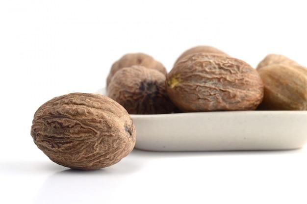 Мускатный орех в белой тарелке на белом фоне