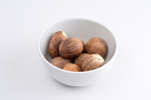 Мускатный орех в белой тарелке, изолированные на белой поверхности