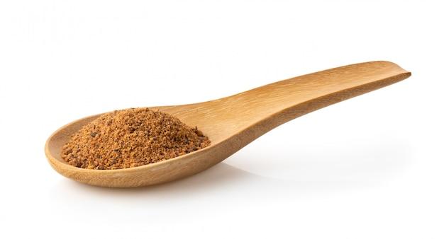 Nutmeg powder in wood spoon on white