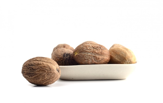 Nutmeg in white plate isolated