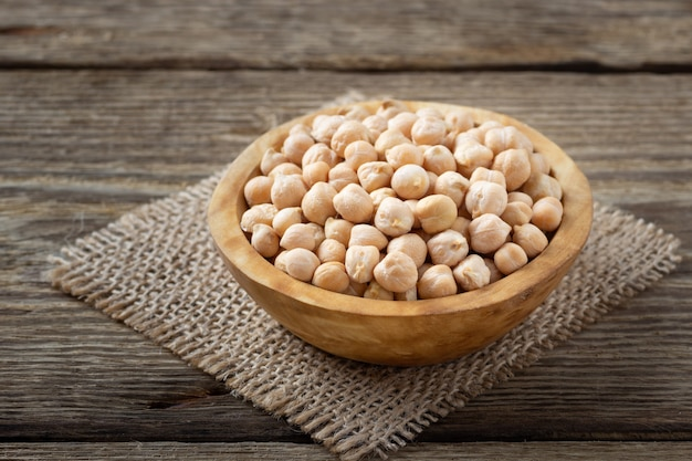Nutrient-dense food - raw chickpeas grains in bowl on a wooden rustic table