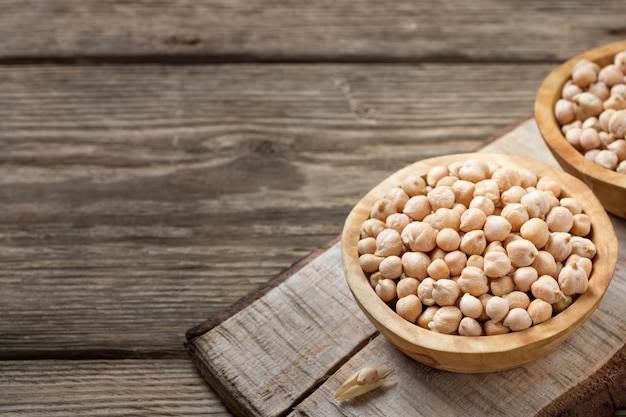 Nutrient-dense food - raw chickpeas grains in bowl on a wooden rustic table.