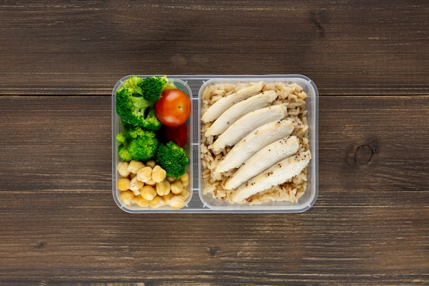 Nutrient dense healthy low fat food in takeaway meal box set on wood background top view