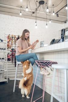 Питание для собак. молодая девушка выбирает еду для своего питомца в зоомагазине