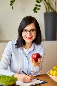 Nutritionist, dietitian woman at the office, hold apple in the hand, healthy vegetables and fruits, healthcare and diet concept. female nutritionist with fruits working at her desk.