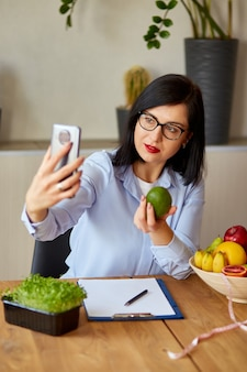 Nutritionist, dietitian woman recording on a smart phone her vlog about healthy eating, healthcare and diet concept. female nutritionist with fruits working at her des at home.