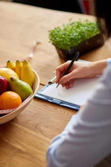 Nutritionist, dietitian woman writing a diet plan, with healthy vegetables and fruits, healthcare and diet concept. female nutritionist with fruits working at her desk, workplace