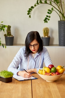 Nutritionist, dietitian woman writing a diet plan, with healthy vegetables and fruits, healthcare and diet concept. female nutritionist with fruits working at her desk.
