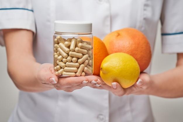 栄養士の医師の健康的なライフスタイルの概念-新鮮な有機柑橘系の果物を保持-グレープフルーツ、オレンジ、レモン、ビタミンカプセルの缶