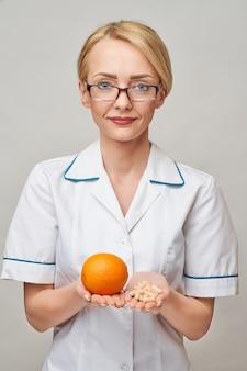栄養士の医師の健康的なライフスタイルの概念-新鮮な有機オレンジフルーツとビタミンカプセルを保持しています