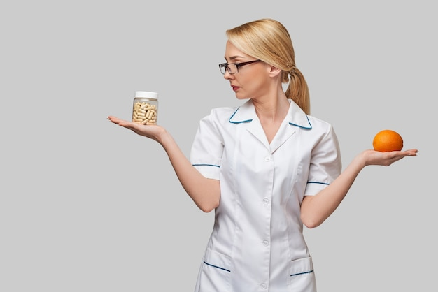 Nutritionist doctor healthy lifestyle concept - holding fresh organic orange fruit and vitamin capsules