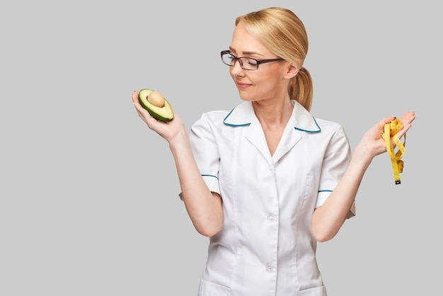 Nutritionist doctor healthy lifestyle concept - holding organic avocado fruit and measure tape