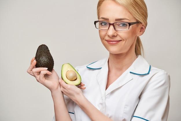栄養士医師の健康的なライフスタイルの概念-有機アボカドの果実を保持
