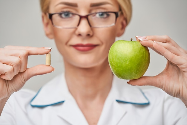 Nutritionist doctor healthy lifestyle concept - holding organic fresh green apple and vitamin capsules