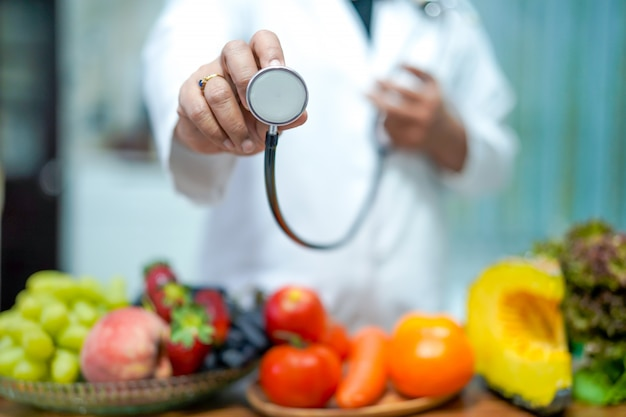 Nutritionist doctor holding orange with various fruits and vegetables.