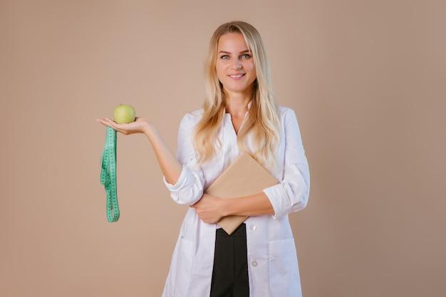 栄養士医師がセンチメートルのリボンを持っています。減量と健康的な食事のコンセプト。